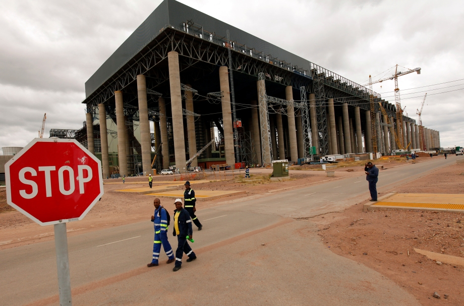Workers walk past the construction site of Medupi power station in Lephalele